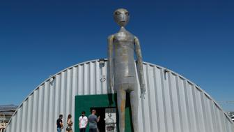 """People enter and exit the Alien Research Center in Hiko, Nev. No one knows what to expect, but lots of people are preparing for """"Storm Area 51"""" on Wednesday, Sept. 18, 2019, in the Nevada desert. Neighbors, elected officials and experts say the craze sparked by an internet joke inviting people to """"""""see them aliens"""" might become a cultural marker, a dud or something in-between. (AP Photo/John Locher)"""
