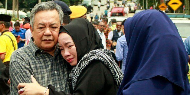 Nik Azlan Nik Abdul Kadir (L), father of one of the victims comforts his wife outside the Darul Quran...