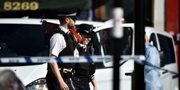 Police officers walk behind cordon tape at the scene of an attack where a man drove a van at muslim worshippers...
