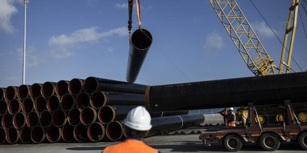 A worker watches as his colleagues use ropes to guide a pipe section for the Trans Adriatic gas pipeline...