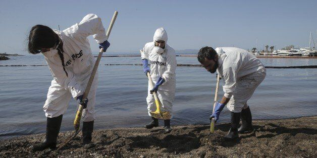 ATHENS, GREECE - SEPTEMBER 15 : Municipality staff shovel oil mixed sand near oil covered sea, spilled...