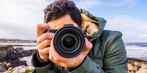 A young man using a DSLR camera at the