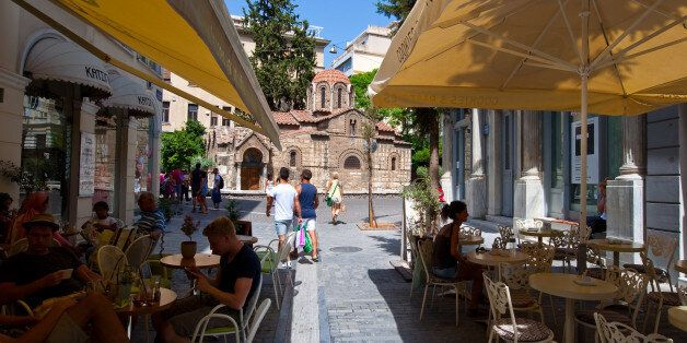 Athens, Greece - August 22, 2014: Traditional outside Greek cafe in Plaka area, customers enjoy their