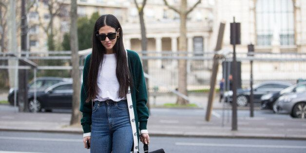 Designer Gilda Ambrosio wears black sunglasses, green cardigan, white top, high-waisted jeans, and and...