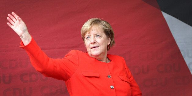 German Chancellor Angela Merkel waves as she arrive to addresse the audience during an election campaign...