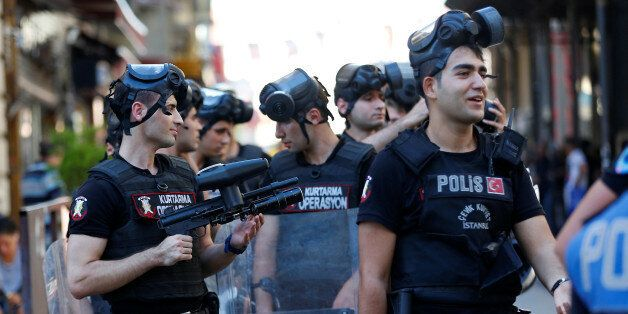 Riot police stand guard as LGBT rights activists try to gather for a pride parade, which was banned by...