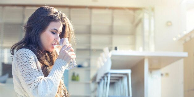 Woman drinking a glass of water. She is sitting on the terrace outside her luxury home. Kitchen in the background. She is smiling. Copy space right hand side