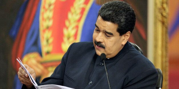 Venezuela's President Nicolas Maduro looks at a book during a news conference at Miraflores Palace in...