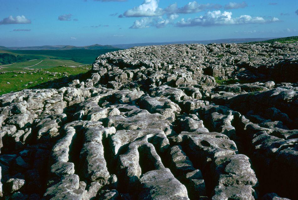 """Harry e Hermione acampam sobre as pedras de calcário da formação rochosa de Malham Cove, em North Yorkshire, em """"Harry Potter e as Relíquias da Morte – Parte 1""""."""