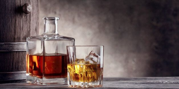 Square decanter and a glass of whiskey with ice on background