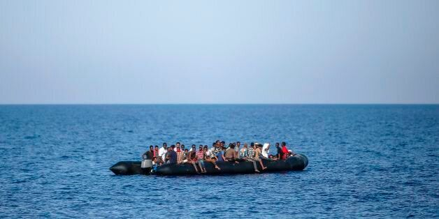 Migrants wait to be rescued by Italian coast guard in the Mediterranean Sea, 30 nautic miles from the...
