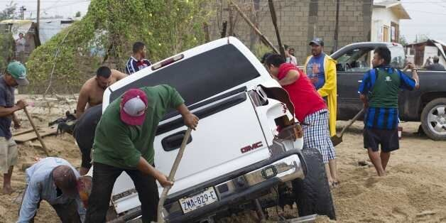 Men attemp to rescue a truck trapped following heavy rains caused by tropical storm Lidia in Los Cabos,...