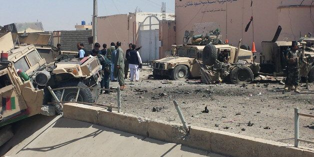 Afghan security personnel inspect the site of a suicide attack near the main police headquarters in Lashkar...