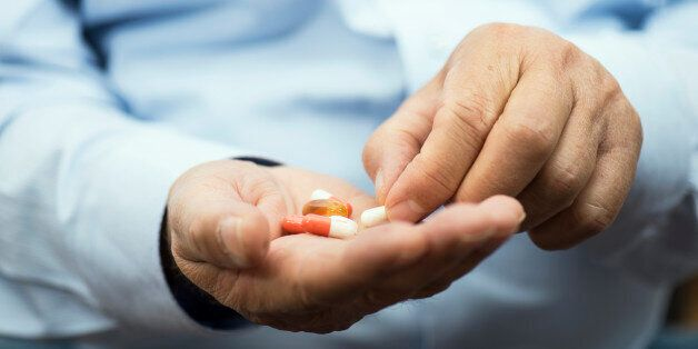 Senior man is holding yellow gel capsules in hand,
