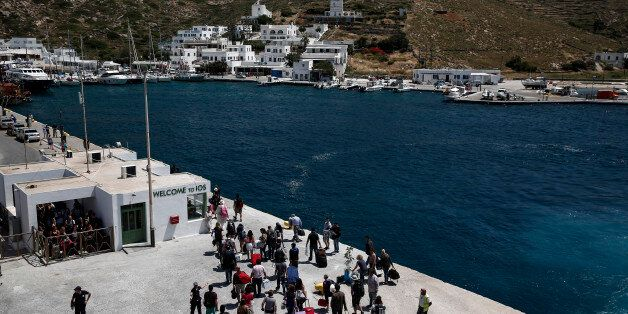Tourists and passengers disembark from a passenger ferry as it arrives at port on the Aegean island of...