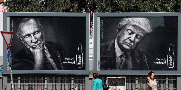 People walk past advertising posters of a German soft drink producer depicting Turkey's President Tayyip...