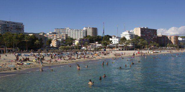 Tourists swim and sunbath at Magaluf's beach in Calvia on Mallorca Island on August 10, 2015. AFP PHOTO/...