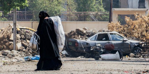 A woman is fleeing from a neighbourhood in western Mosul where fights between the federal Police and...