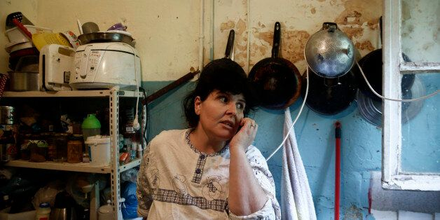 Emine Kilic, a Turkish squatter and mother of 10, speaks on the phone inside a kitchen at