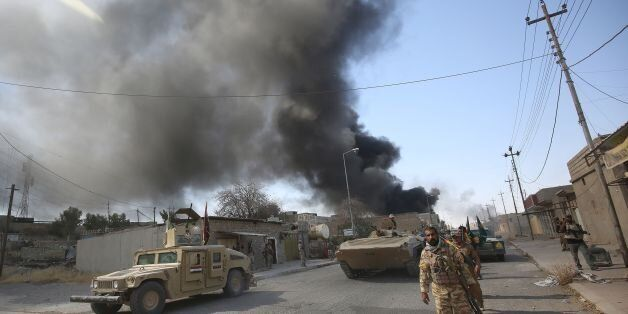 Smoke billows in the background as members of the Iraqi forces, backed by the Hashed Al-Shaabi (Popular...