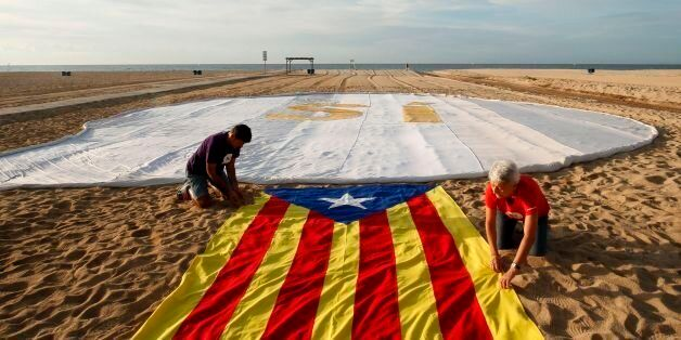 Two people unfold an 'Estelada' (Pro-independence Catalan flag) beside a banner reading 'SI' (Yes) on...