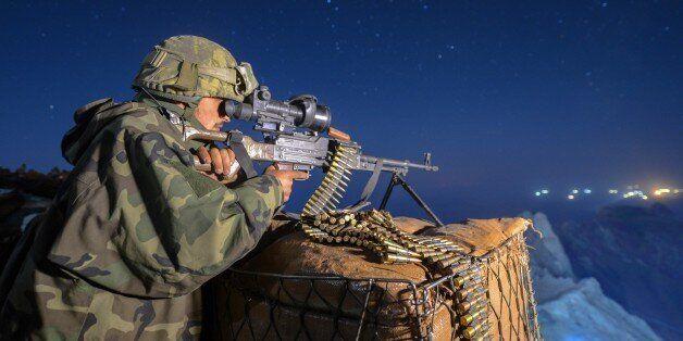 HAKKARI, TURKEY - AUGUST 15: A Turkish soldier looks through binoculars weapon at observation post at...