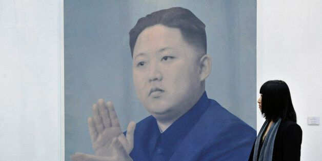 A visitor looks at a portrait of the leader of the Democratic People's Republic of Korea (DPRK) Kim Jong-un...