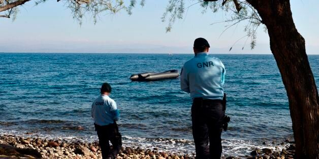 Portugese officers serving for the European Border and Coast Guard Agency look at a rubber boat from...