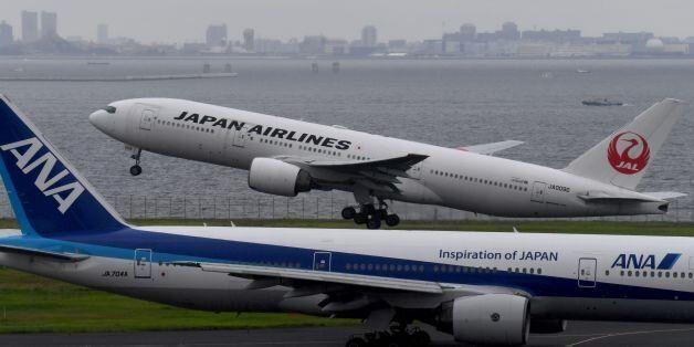 A Japan Airlines (JAL) Boeing 777 jetliner takes off beside All Nippon Airways (ANA) jetliner at Haneda...
