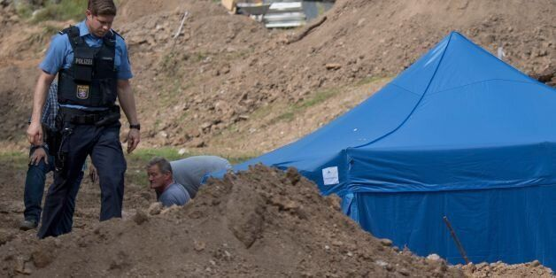 A policeman walks past a blue tent covering a British World War II bomb that was found during construction...