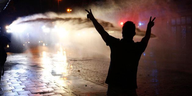A protester shows V-sign as German police use water cannon during the demonstration at the G20 summit...