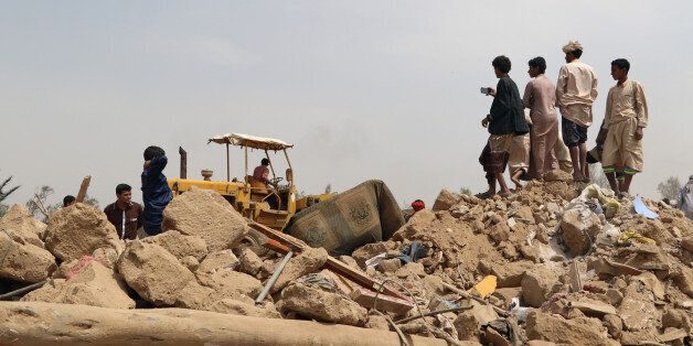 People stand on the debris of a house at the site of a Saudi-led air strike on an outskirt of the northwestern...