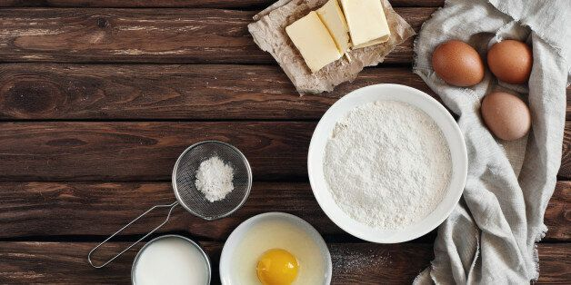 ingredients for making pancakes or cake - flour, egg, butter, milk on  the old wooden background. top view. rustic or rural style. background with free text space.  Ingredients for the dough.