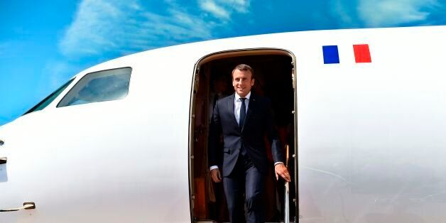 French President Emmanuel Macron disembarks from the airplane upon his arrival on August 23, 2017 at...