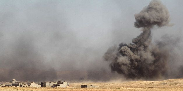 Smoke rises in the background as Iraqi forces backed by the Hashed Al-Shaabi (Popular Mobilization units)...