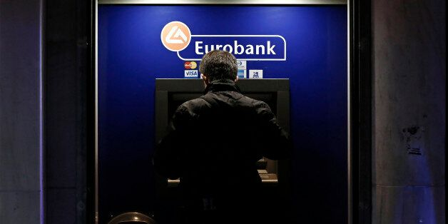 A customer uses an automated teller machines (ATM) operated by Eurobank Ergasias SA at night in Athens,...