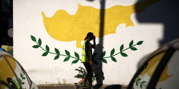 A man walks past a Cypriot flag painted on a wall in Nicosia, Cyprus July 7, 2017. REUTERS/Yiannis