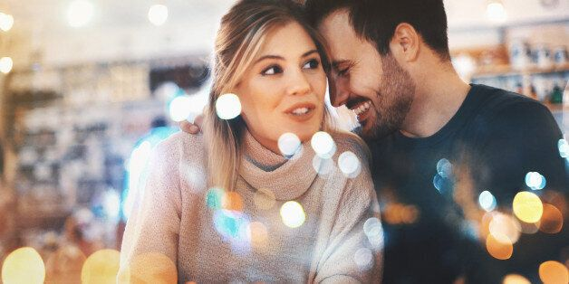 Closeup of happy mid 20's couple having fun at local coffee place on winter night, somewhere around Christmas time.They are sitting by a window side by side and laughing. The woman is looking through the window. Both wearing warm casual clothing. Tilt shot,toned image.