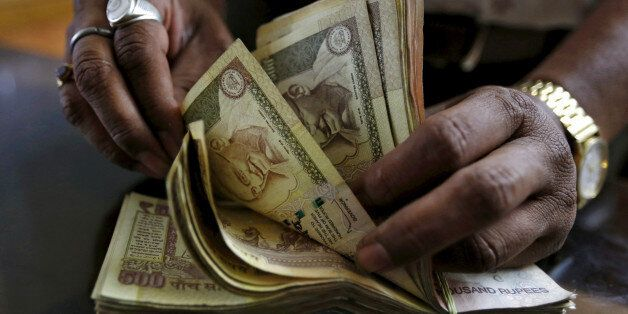 A money lender counts Indian rupee currency notes at his shop in Ahmedabad, India May 6, 2015. REUTERS/Amit...