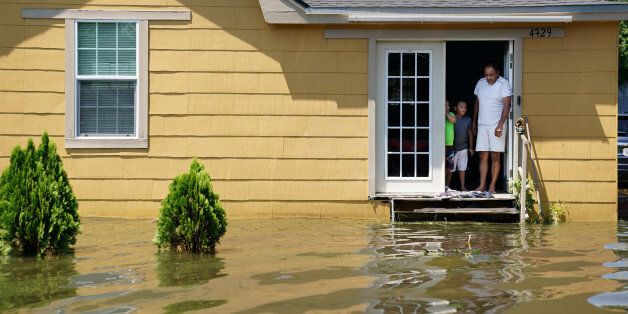 A family stand in the door of their flooded house in Port Arthur, Texas, U.S., August 31, 2017. REUTERS/Carlo
