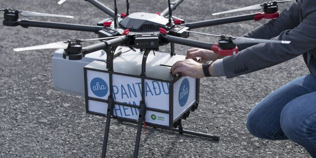 Maron Kristofersson, chief executive officer of Aha, handles a package secured to a drone manufactured...