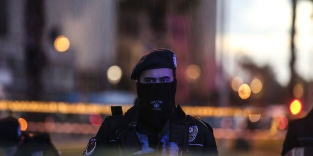A Turkish police officer stands guard at the site of an explosion in front of the courthouse in Izmir...