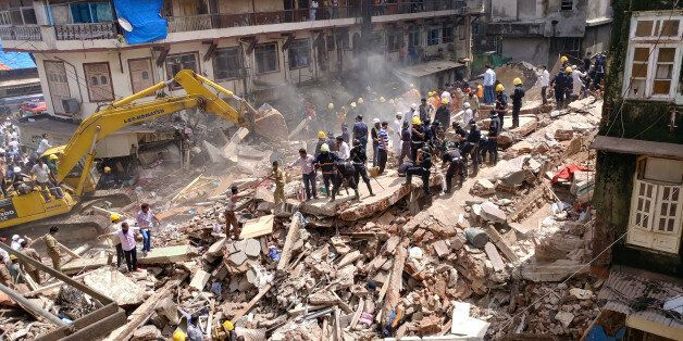 Firefighters and rescue workers search for survivors at the site of a collapsed building in Mumbai, India,...