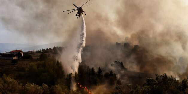TOPSHOT - A firefighting helicopter drops water on a fire burning east of the Greek capital Athens on...