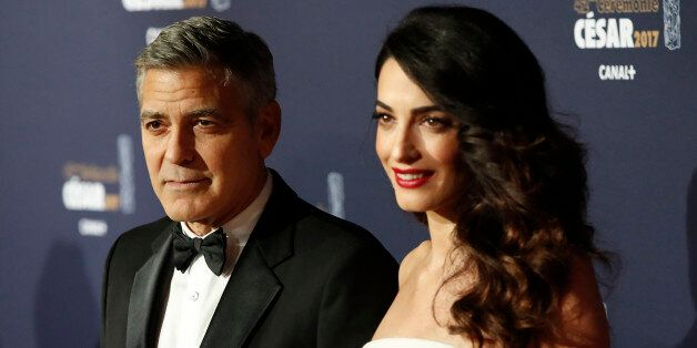 Actor George Clooney and his wife Amal pose as they arrive at the 42nd Cesar Awards ceremony in Paris, France, February 24, 2017. REUTERS/Gonzalo Fuentes