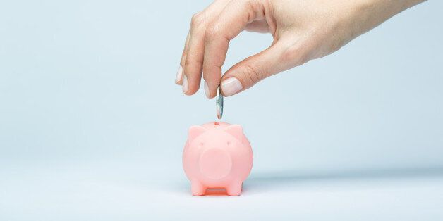 Female hand putting a coin into piggy bank. Light blue background, soft shadow. Canon 5D MK