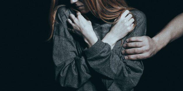 Fearful rape victim, man holding her arm, black