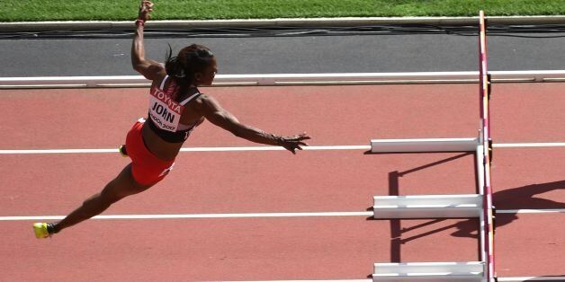 Trinidad and Tobago's Deborah John (L) falls as she competes in the women's 100m hurdles athletics event...