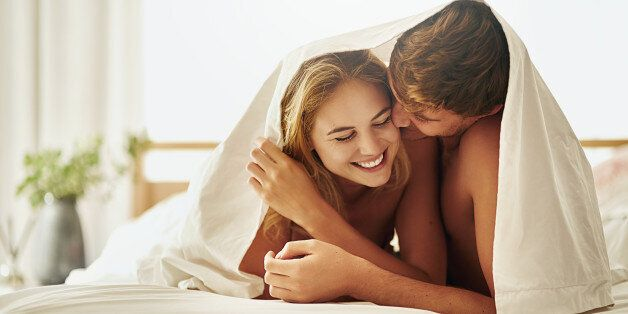 Shot of a young couple sharing an intimate moment under the covers in bed