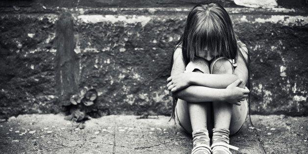 Depressed child sitting at weargered sidewalk. Fine noise